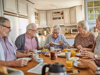 Seniorenwohnungen, Senioren sitzen zusammen beim Essen, Foto: iStock.com/Geber86