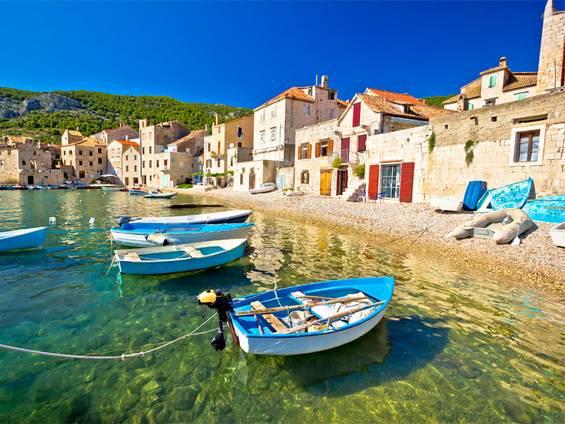 Immobilienkauf Kroatien, die Häuser von Komiza sind bis unmittelbar an den Strand gebaut, Blick vom Wasser aus, Foto: xbrchx / iStock