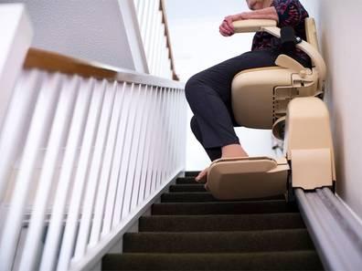 Seniorenwohnungen, Senior fährt mit dem Treppenlift die Treppe hinunter, Foto: iStock.com/Daisy-Daisy