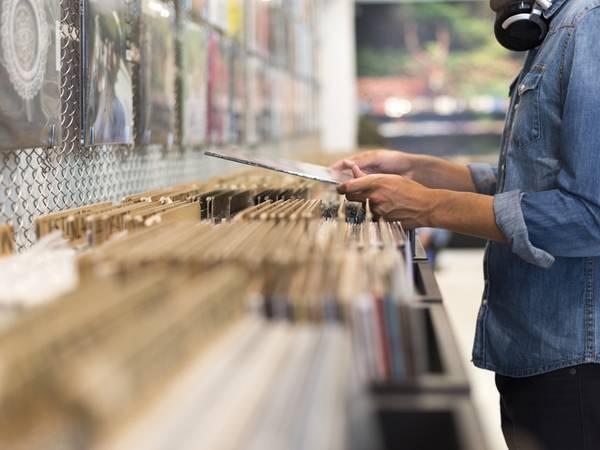 Gerwerbeimmobilie, Plattenladen, ein Mann sucht in einem Plattenladen in der Auslage, Foto: iStock.com/LDProd