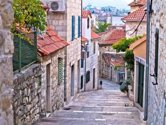 Immobilienkauf Kroatien, Blick eine schmale Gasse entlang, alte Steinhäuser, Foto: xbrchx / iStock